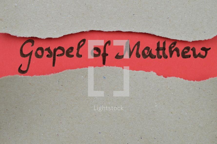 Gospel of Matthew - torn open kraft paper over light red paper with the name of the Gospel of Matthew