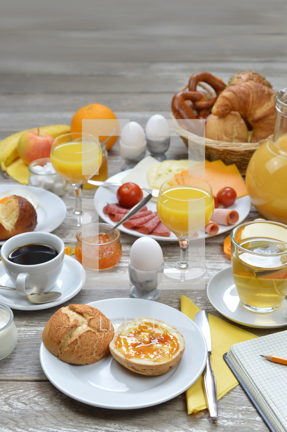 breakfast table with lots of fresh food like coffee, rolls, cheese, eggs, orange juice, tea, jam, butter, banana, apple, orange and a basket full of croissant, rolls and pretzel with copy space above