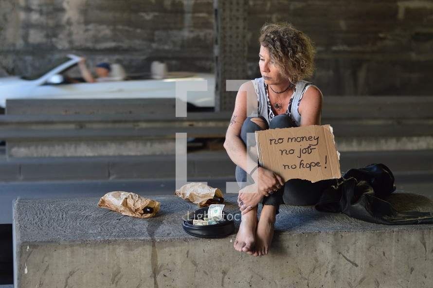 a woman sitting under a bridge with bottle of alcohol holding a sign