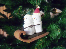 A couple of snowmen or snow people  sleigh riding on a sleigh Christmas ornament hanging on a Christmas tree showing an animated happy Christmas couple sleigh riding together.