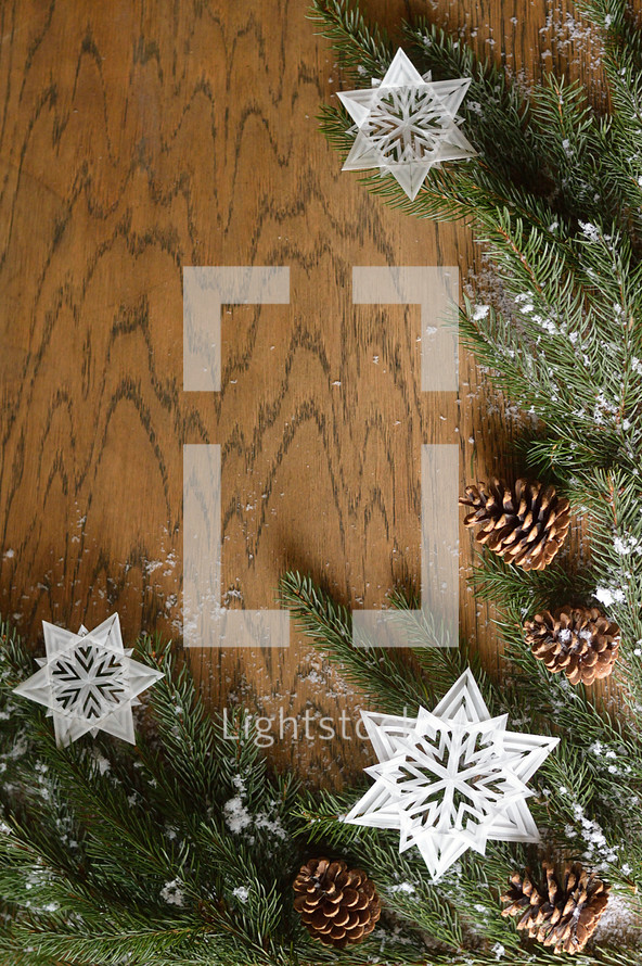 star ornaments, pine cones, snow, and pine boughs on a wooden  background