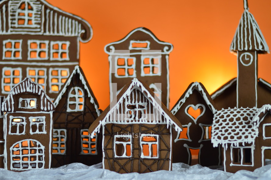 home made gingerbread village in front of orange background on white snowlike velvet as advent decoration
