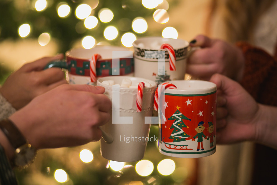 Four Christmas cups with hot cocoa and candy canes are put together to make a toast.