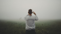 a man with a cellphone taking a picture of fog