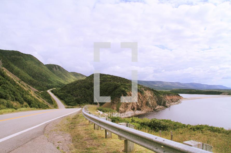 Winding road through hillside next to ocean.