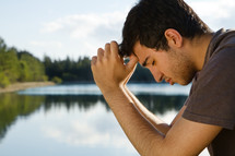 man praying by a lake