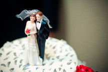 Bride and groom figurine on a wedding cake.