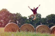 man jumping on hay bales