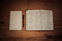 blank notebook, pen, and open Bible
