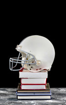 football helmet on a stack of books