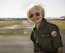 a boy child in a pilot uniform standing in front of a runway