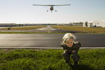 a boy child ducking as a plane flies over a runway