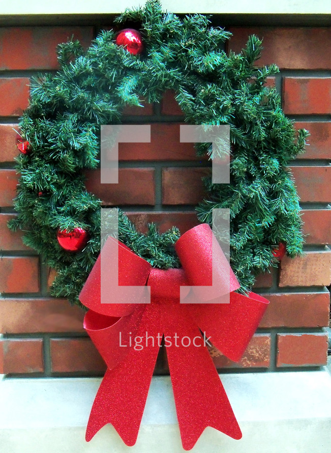 A  traditional old fashioned green evergreen Christmas wreath with a red bow ribbon against a brick hearth background reminding viewers that the Christmas season is here.