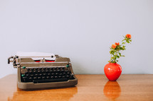 typewriter and flowers in a vase on a desk