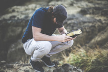 a man squatting with head bowed in prayer holding a Bible