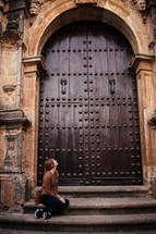 a woman sitting on steps looking up at large wooden doors at the entrance to a church