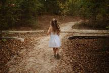 a little girl running on a dirt path