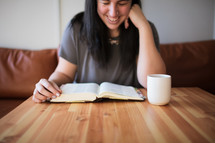 a young woman reading a Bible at a coffee shop