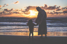 Jesus standing on a beach holding hands with a little girl