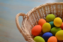 Colorfully painted Easter eggs on straw in a basket on a wooden table