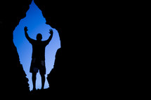 silhouette of a man with raised hands standing in the mouth of a cave