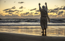 Jesus standing with raised hands on a shore at sunset