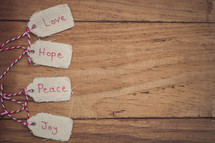 "Christmas gift tags, reading ""Love,"" ""Hope,"" ""Peace,"" and ""Joy,"" on a wood grain background."