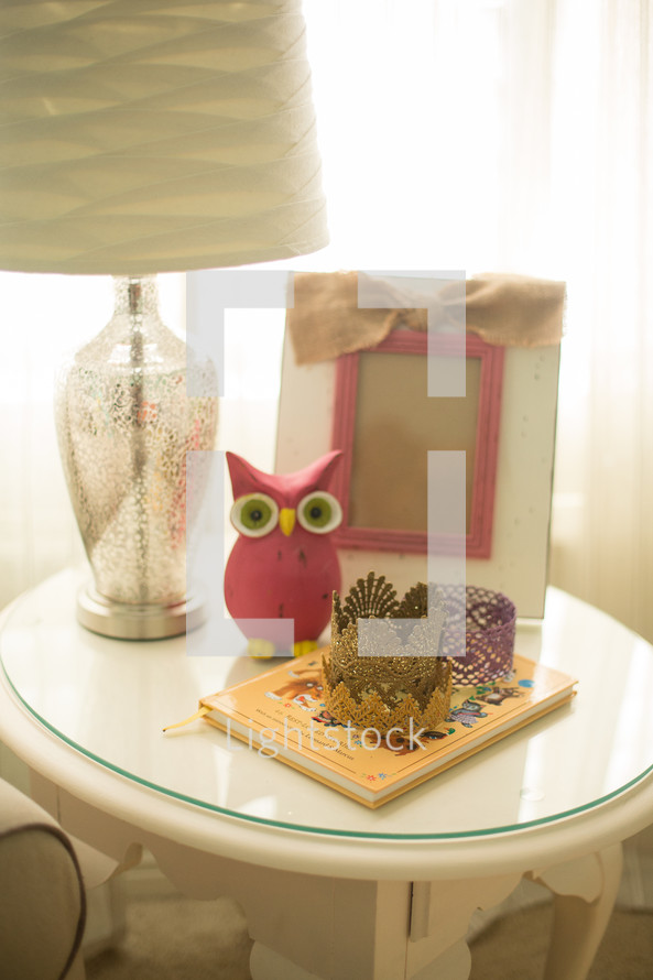 frame, owl figurine, book, and lamp on an end table