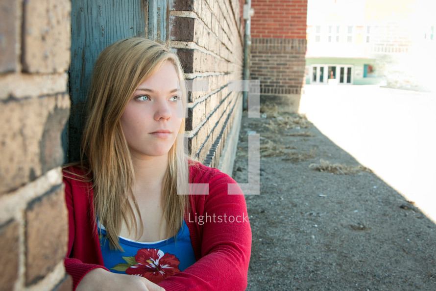 teen girl sitting against a wall outdoors