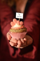 Woman offering a cupcake with pink hearts and a sign saying TE AMO.