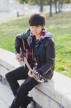 a teen boy playing a guitar
