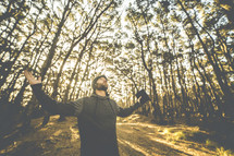 a man with outstretched arms holding a Bible looking up to God in a forest
