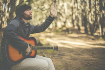 a man in a forest with a guitar and raised hand praising God