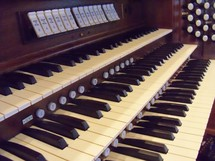 organ keys belonging to an old pipe organ in a church sanctuary.
