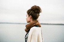 a woman in a scarf standing by a lake