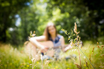 blurry image of a woman sitting in a field playing a guitar