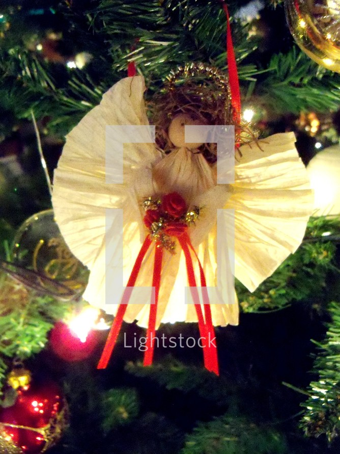 An old fashioned paper Christmas angel ornament on a Christmas tree to celebrate the Christmas holidays.