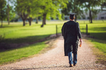 Graduate walking on dirt road holding a Bible.