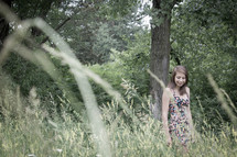 woman walking in a field of tall grass