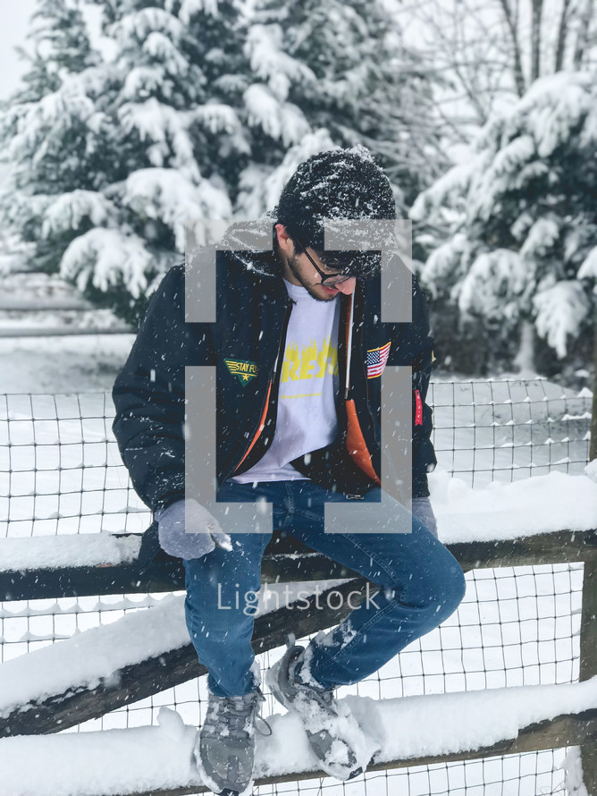 a man sitting on a fence in the snow