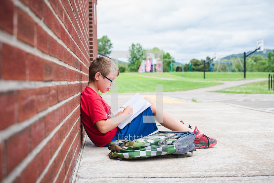 a young boy leaning against a school building doing his homework