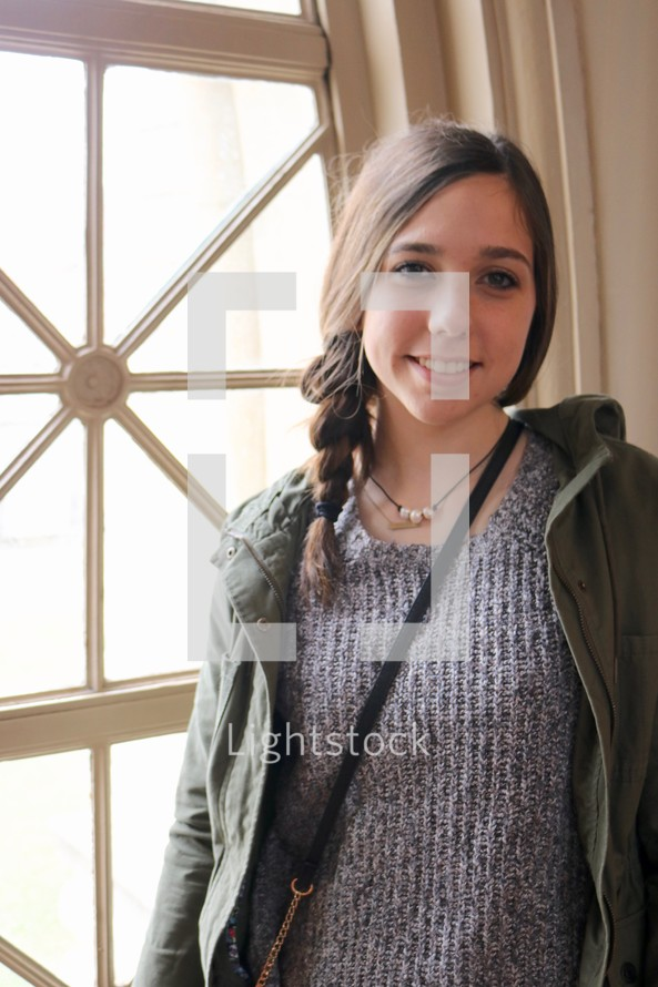 smiling teenage girl standing by a window
