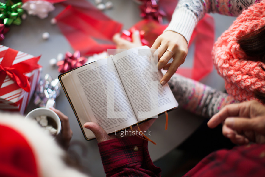An open Bible on a table with Christmas decorations