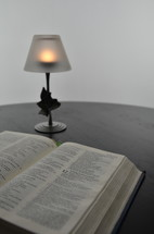 votive candle shaded lamp and an open Bible