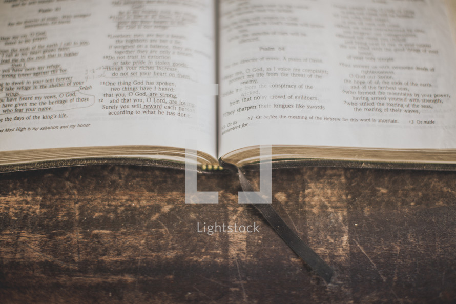 An open Bible and bookmark on wood