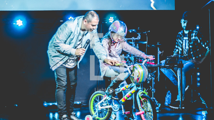 a child giving a bike on stage