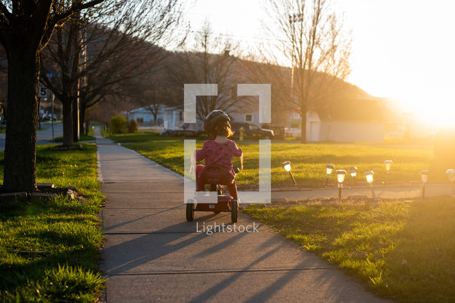 toddler girl riding a tricycle