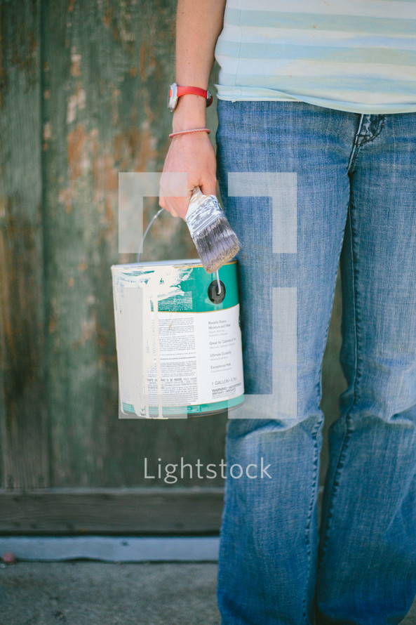 Person holding a old paint can and paint brush standing in front of an old green wooden wall