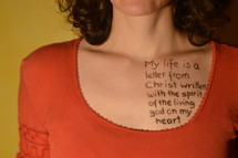 A woman with a scripture written on her chest in ink.