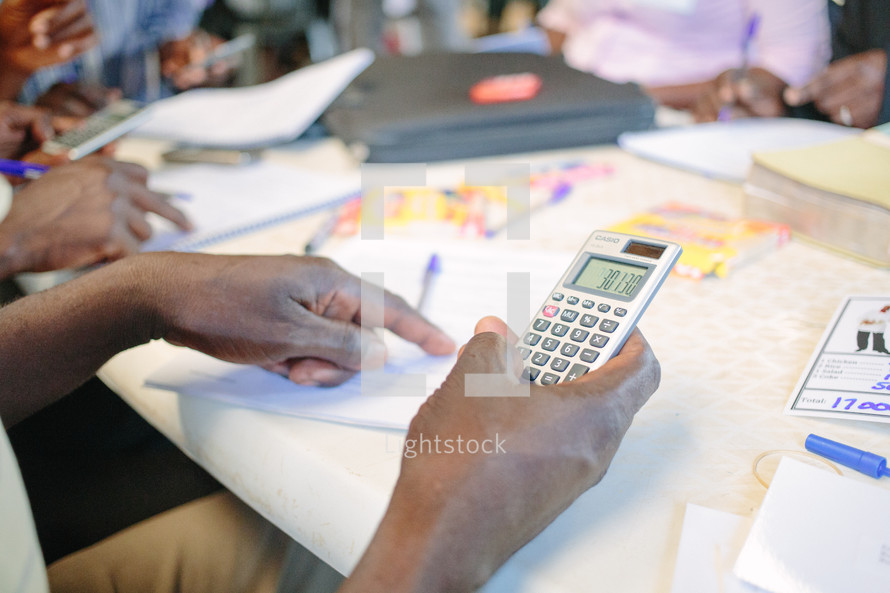 a woman holding a calculator, a man holding a calculator, education in business, training,